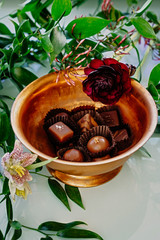 Chocolates in a bowl surrounded by flowers