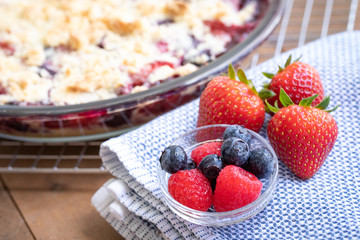 Close up on fresh spring berries, with a berry pie in the background