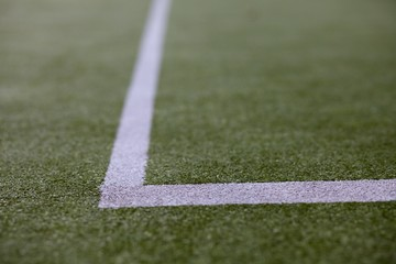 White lines marking out a tennis court on astro turf