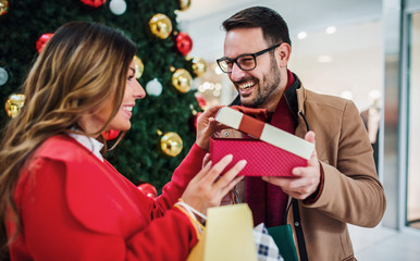 Christmas surprise for a girlfriend. Young couple shopping together in shopping mall. Consumerism, love, dating, lifestyle concept