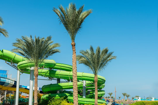 Colorful slides and pool in aqua park. Place to have a rest and family fun. Long, green waterslide in aqua park. sunny day