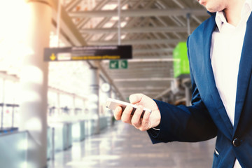 Businessman in a blue jacket and white shirt at the airport holds a smartphone in his hand