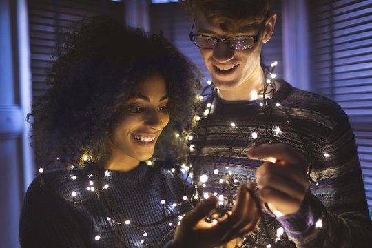 Smiling couple playing with fairy lights at home