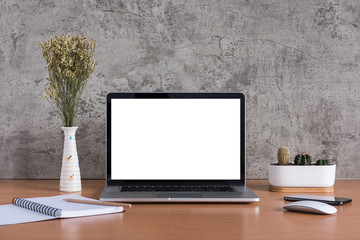 Blank screen of laptop computer with note book, pencil, dry flowers, Smart phone and cactus vase on raw concrete background