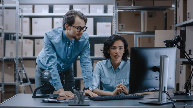 Male and Female Warehouse Inventory Managers Talking, Solving Problems, Using Personal Computer and Checking Stock. In the Background Rows of Shelves Full of Cardboard Box Packages.