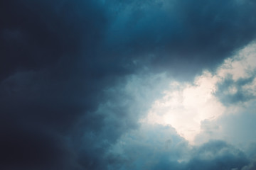 Sun shining through dark blue dramatic clouds in sky. Copy space. For background, wallpaper