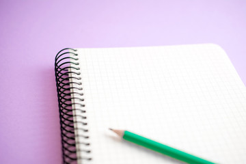 notepad on a spring with green pencil purple background. business concept