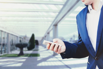Businessman in a blue jacket and white shirt holding a smartphone in his hand on the background in the business center