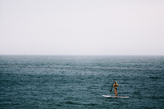 Woman standing on a surfboard in the middle of the ocean