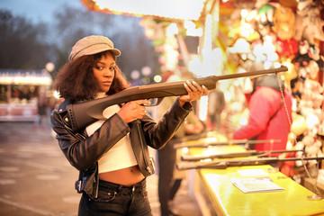 Beautiful girl with a fake gun in a luna park