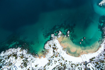 Aerial of the ocean and a snow covered beach