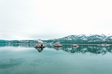 Piles of rocks in the middle of the water with snow covered mountains in the distance