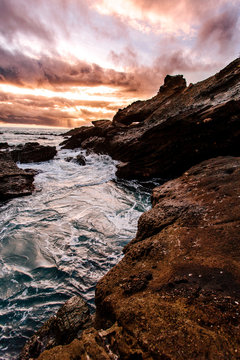 Water surrounded by rocks during sunset
