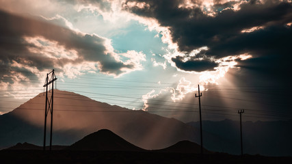 Telephone poles with mountains in the background and billowing clouds