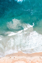 Aerial of beach waves crashing on the shore