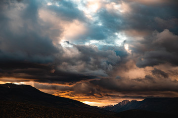 Clouds billowing over mountains during sunset