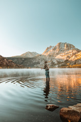 Person fishing with mountains in the distance