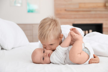 Cute boy kissing his little sister on bed at home