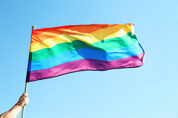Gay man holding rainbow LGBT flag on blue sky background