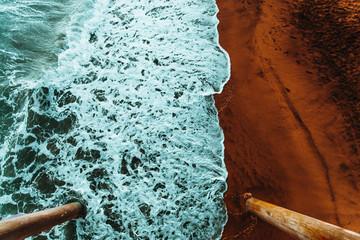 Looking down upon ocean waves crashing along the shore