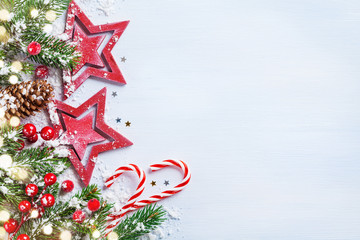 Christmas background with stars, snowy fir branches, cones and bokeh lights. Holiday banner or card.