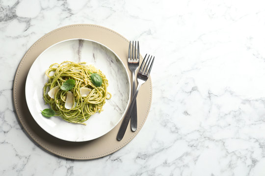 Flat lay composition with plate of delicious basil pesto pasta and space for text on marble table