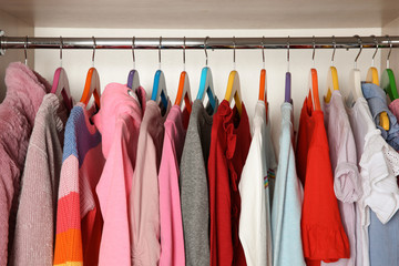 Wardrobe with stylish girl's clothes hanging on rack