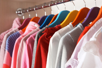 Stylish girl's clothes hanging in wardrobe, closeup