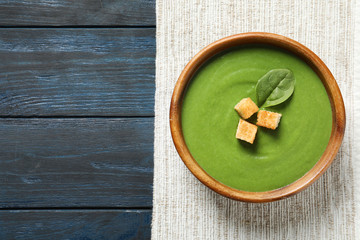 Fresh vegetable detox soup made of spinach with croutons in dish and space for text on wooden background, top view