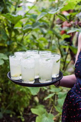 Woman carrying a tray of moonshine whiskey cocktails