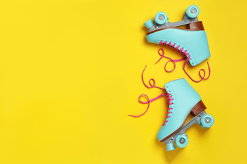 Pair of stylish quad roller skates on color background, top view with space for text
