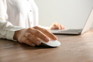 Woman using computer mouse with laptop at table, closeup