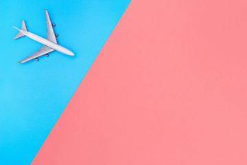 white toy plane on blue and pink yellow background
