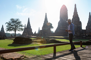 Travel and tourism. Men traveling in Thailand. Male travelling in ruins of Ancient Ayutthaya. Young caucasian man walk on a wooden bridge in the morning at temple in old city of Ayutthaya in Thailand.