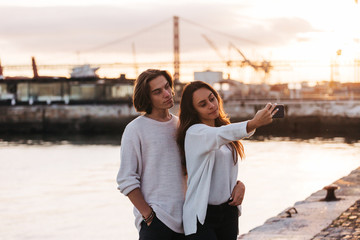 Young man and woman taking selfie on smartphone near water