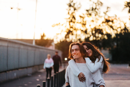 Young happy woman on back of man walking on street