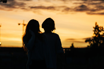 Young woman near man at sunset on street