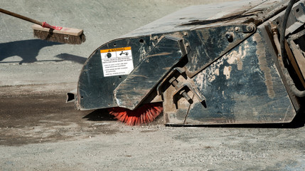 Sweeper attachments mini excavator. The sweeper sweeps, collects and dumps dirt and debris.