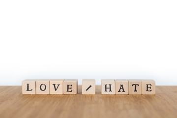 "Focus on the words ""Love / Hate"" made of wooden block dice with letters on a wooden table. Shallow depth of field. Copy space."