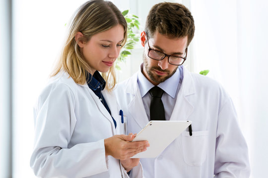Concentrate young confident doctors looking medical reports in digital tablet in medical office.