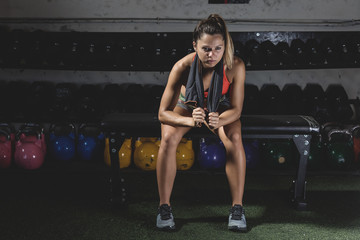 Concentrated woman sitting on bench near kettle bells and dumbbells on shelves