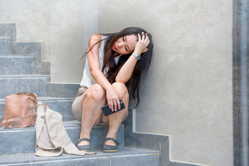 depressed and desperate Asian Chinese businesswoman crying alone sitting on street staircase suffering stress and depression crisis being victim of mobbing or fired