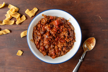 bowl of chili with beans and tomatoes with side of corn chips flat lay