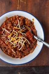 bowl of chili with beans and tomatoes topped with shredded cheese flat lay