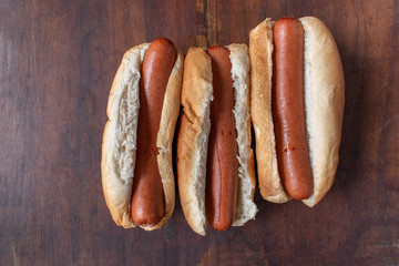 row of plain hot dogs in buns flat lay on wood table