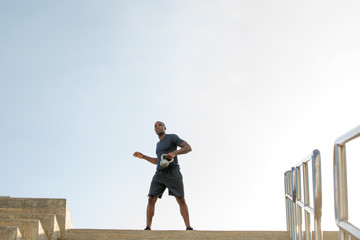 Man doing kettlebell swings on the Miami Beach