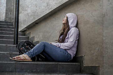 depressed Asian Japanese student woman or bullied teenager girl sitting outdoors on street staircase victim of bullying feeling scared and stressed suffering depression