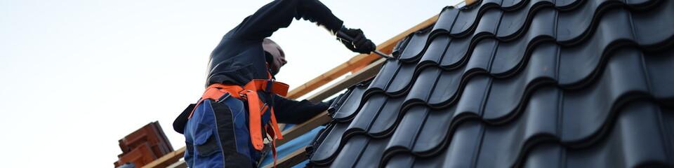 Dachdecker bei der Arbeit mit schwarzen Dachsteinen, web slider Fototapete