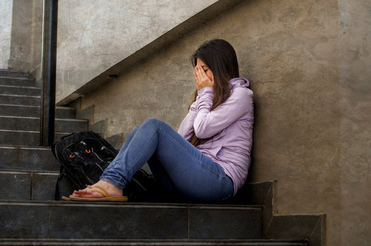 depressed student woman or bullied teenager girl sitting outdoors on street staircase scared and anxious victim of bullying feeling desperate suffering depression