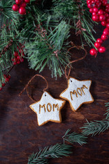hand painted Christmas star ornaments for two moms on festive wood table